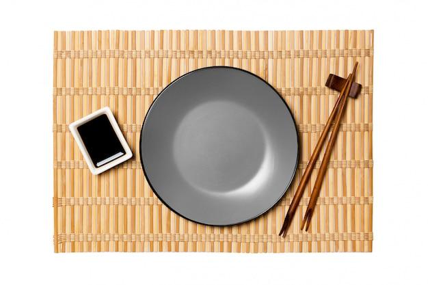 Piatto grigio rotondo vuoto con le bacchette per sushi e salsa di soia sulla stuoia di bambù giallo. vista dall'alto con copyspace