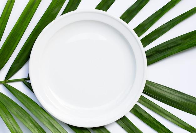 Piatto in ceramica bianco vuoto su foglie di palma tropicale su bianco