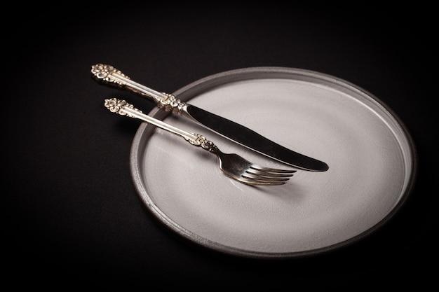 Piatto in ceramica grigia rotonda vuota su sfondo nero con forchetta e coltello vintage cupronickel
