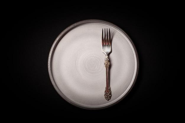 Piatto in ceramica grigia rotonda vuota su sfondo nero con forchetta vintage cupronickel