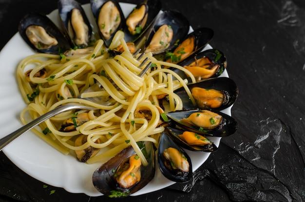 Piatto italiano con cozze al vapore con vino. chiuda in su degli spaghetti su una forcella. concetto di mangiare frutti di mare. messa a fuoco selettiva.