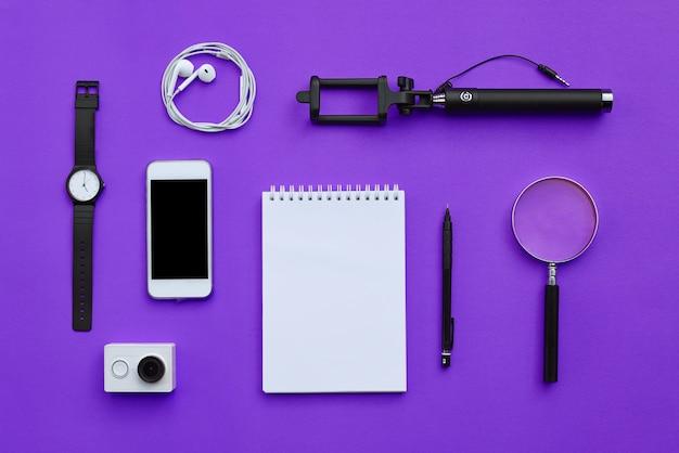 Piatto laici di accessori su sfondo viola scrivania