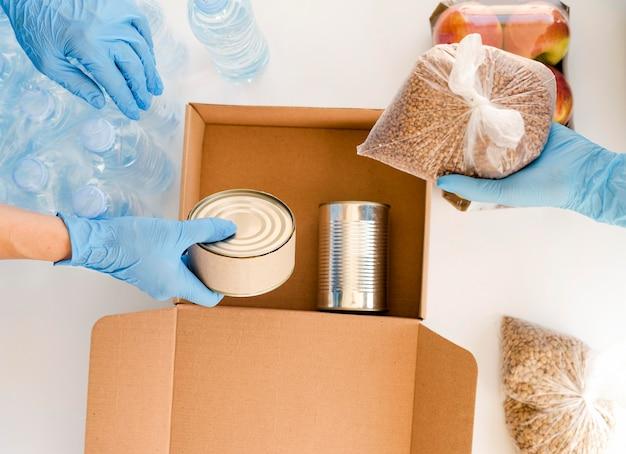 Piatto laici di persone che preparano scatola con donazione di cibo