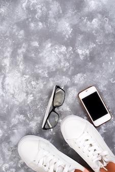 Piatto laici di scarpe da tennis bianche su sfondo di pietra con telefono e cuffie.