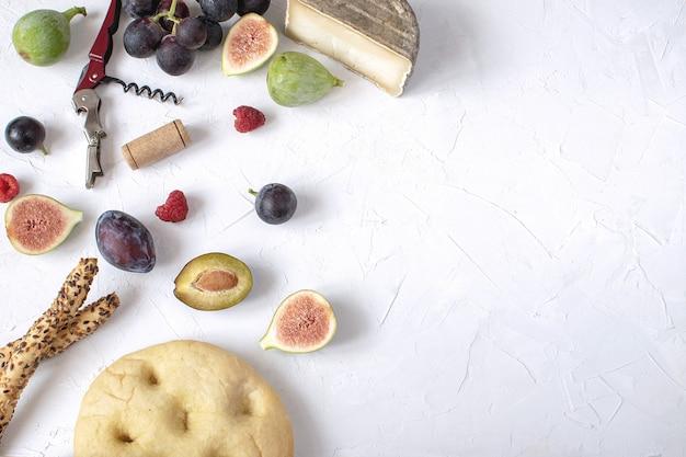 Piatto lay antipasto di vino fico prosciutto uva prugna formaggio focaccia grissini