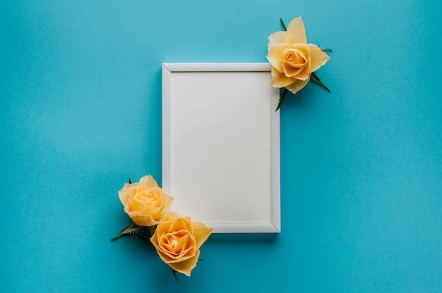 Piatto lay - cornice bianca vuota con rose gialle su un blu. copia spazio, mock up. concetto di primavera.