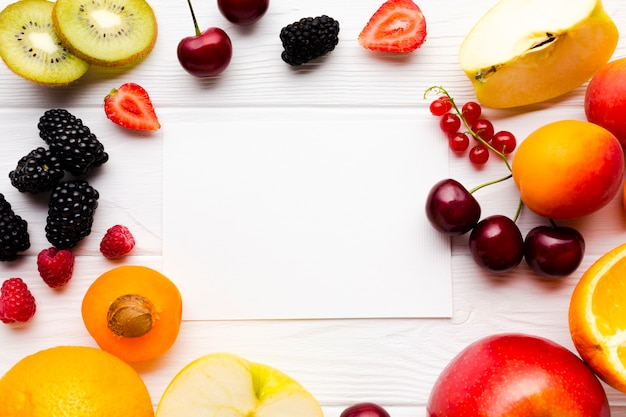 Piatto-lay di bacche fresche e frutta con la carta