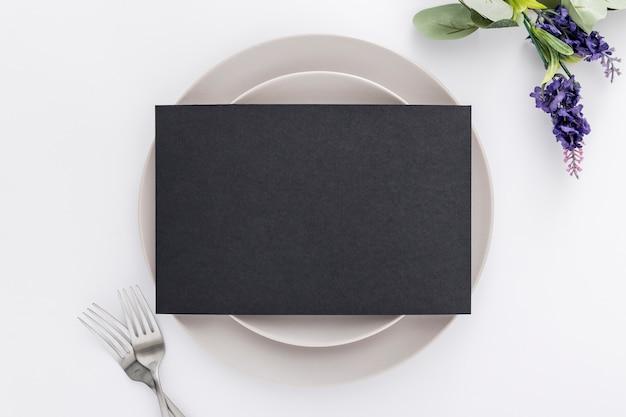 Piatto lay di carta menu vuoto su piatti con forchette e fiori