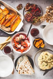 Piatto lay di cibo vegano: patate dolci al forno, cavolfiore, frutta, insalata di verdure e tortilla con verdure su sfondo bianco.
