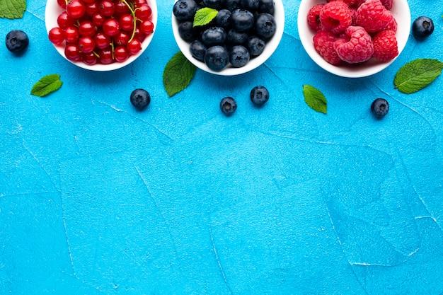 Piatto-lay di ciotole di frutti di bosco con spazio di copia