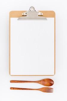Piatto lay di menu vuoto con posate in legno