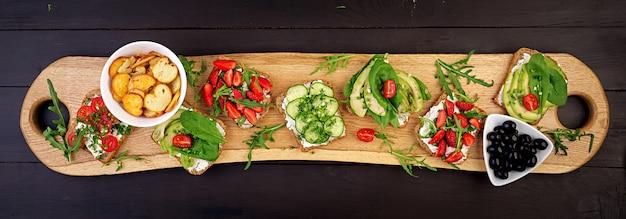 Piatto lay di sano tavolo da pranzo vegetariano. panini con pomodoro, cetriolo, avocado, fragola, erbe e olive, snack. banner. mangiare pulito, cibo vegano