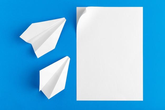 Piatto lay di un aereo di carta sul colore blu pastello