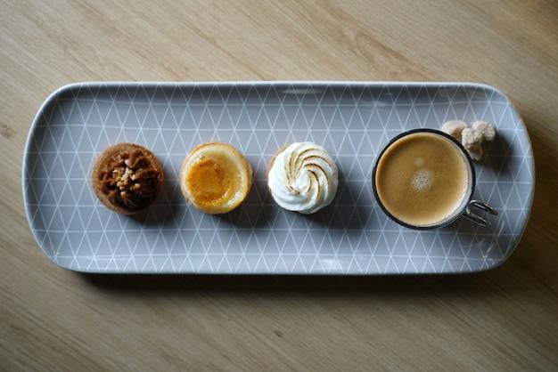 Piatto lungo che serve caffè e tre deliziosi mini dessert