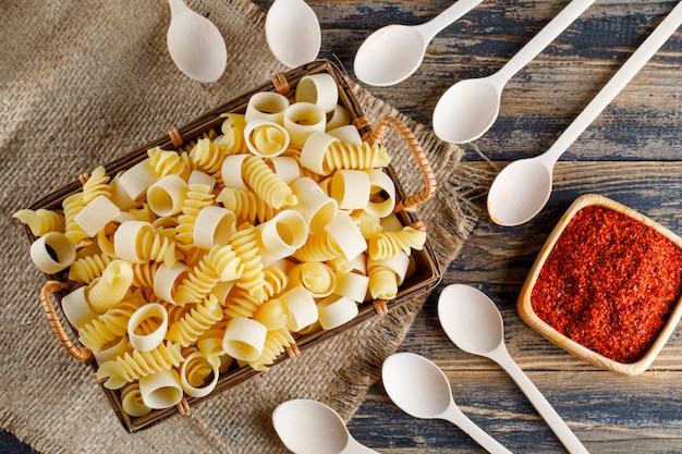 Piatto maccheroni maccheroni pasta nel vassoio con cucchiai, spezie rosse su tela di sacco e fondo in legno. orizzontale