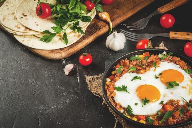Piatto messicano tradizionale huevos rancheros - uova strapazzate con salsa di pomodoro, tortillas di taco, verdure fresche e prezzemolo. colazione per due. su un tavolo di cemento nero. con una forchetta, copia spazio
