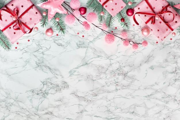 Piatto natalizio panoramico disteso su marmo bianco con bordo costituito da scatole regalo incartate, ramoscelli di abete verde naturale, bigiotteria bordeaux e rosa, copia-spazio