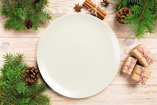 Piatto opaco bianco vuoto su legno con decorazione natalizia, piatto tondo,
