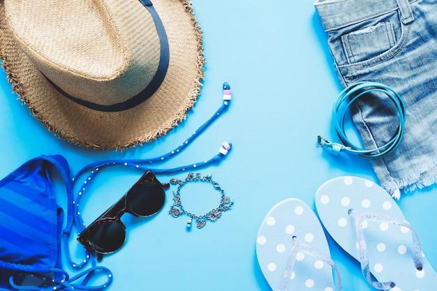 Piatto piano di accessori femminili su sfondo blu, concetto di moda primavera e estate