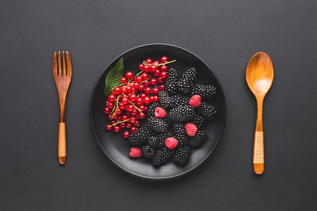 Piatto piano di bacche con cucchiaio e forchetta