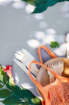 Piatto piano di carta ecologica e stoviglie in legno, luce solare estiva, rifiuti zero, vita ecologica e senza plastica, bicchieri di carta, piatti, borsa, piatti e posate in legno in sacchetto di rete di cotone.