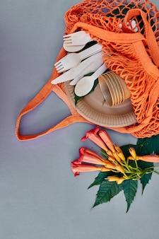 Piatto piano di carta ecologica e stoviglie in legno, rifiuti zero, vita senza plastica ed ecologica, bicchieri di carta, piatti, borsa, piatti e posate in legno in sacchetto di rete di cotone.