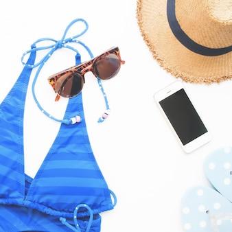 Piatto piano di oggetti di spiaggia e smart phone, concetto estivo su sfondo bianco con copia spazio