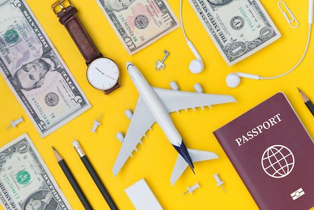 Piatto piano di pianificazione del viaggio con aereo, matita, orologio, denaro, nota cartacea, auricolare e passaporto
