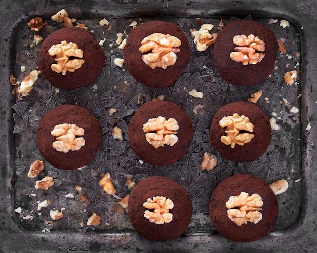 Piatto piatto di palle di rum con noci su teglia scura con fiocchi di cioccolato e nuances schiacciate