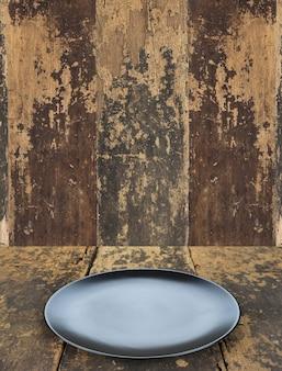 Piatto piatto vuoto sul fondo della tavola in legno