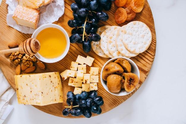 Piatto posare con vari tipi di formaggio, uva, noci, miele e cracker in tavola di legno su marmo