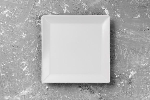 Piatto quadrato sullo sfondo di un tavolo grigio