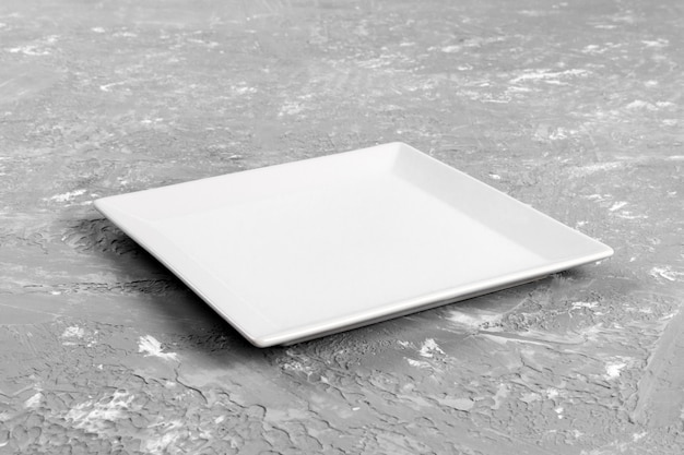 Piatto rettangolare vuoto sul fondo grigio della tavola