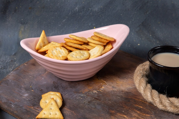Piatto rosa vista frontale con cracker salati e tazza di latte su gray