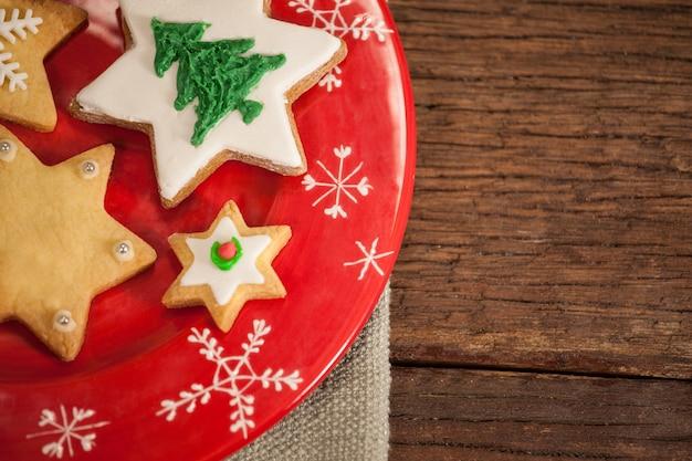 Piatto rosso con i biscotti a forma di albero di natale