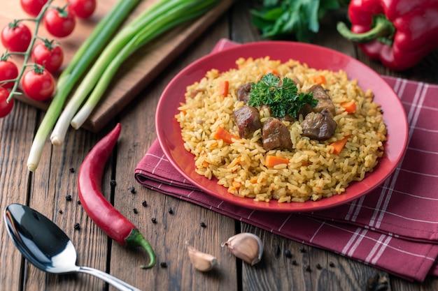Piatto rosso con pilaf su un rustico tavolo in legno marrone. sul tavolo ci sono pepe rosso, cipolle verdi, aglio, pomodorini, tovagliolo rosso, cucchiaio.