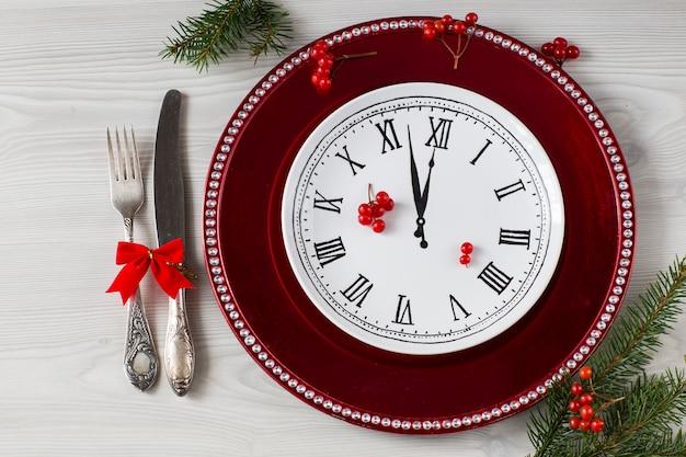Piatto rosso e un piatto bianco con l'immagine di un orologio e posate, bacche rosse e rami di abete