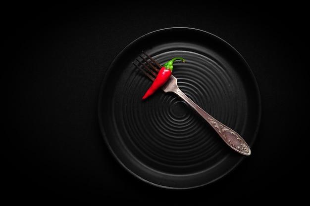 Piatto rotondo in ceramica nera con motivo a cerchi con peperoncino rosso fresco