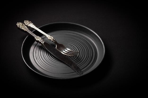 Piatto rotondo in ceramica nera invecchiata con posate vintage