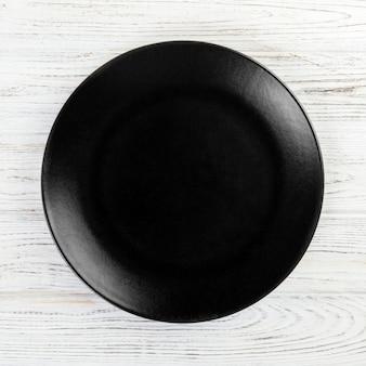Piatto rotondo nero su fondo di legno, vista dall'alto, spazio di copia