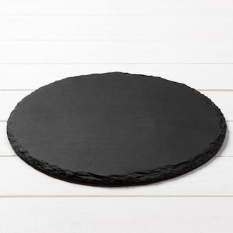 Piatto rotondo nero su legno, vista dall'alto, copia spazio