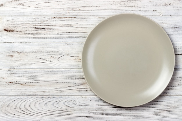 Piatto rotondo opaco vuoto sulla tavola di legno