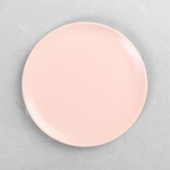 Piatto rotondo rosa vuoto sulla tavola di legno