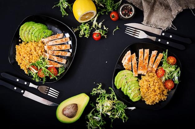 Piatto sano con pollo, pomodori, avocado, lattuga e lenticchie su sfondo scuro.