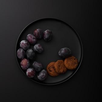 Piatto scuro con biscotti e prugne su uno sfondo scuro