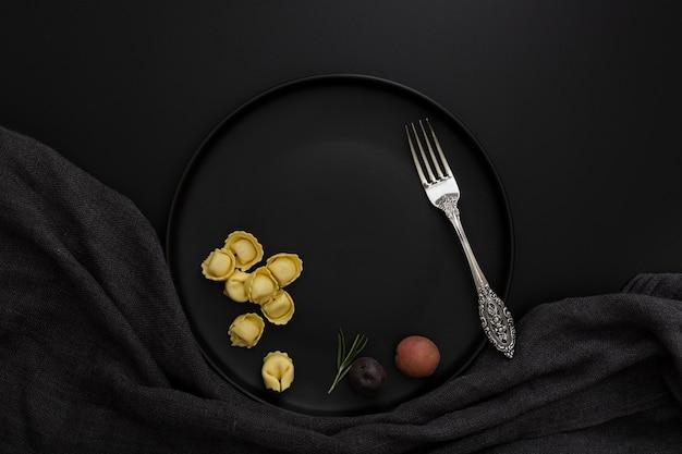 Piatto scuro con tortellini e forchetta su sfondo nero