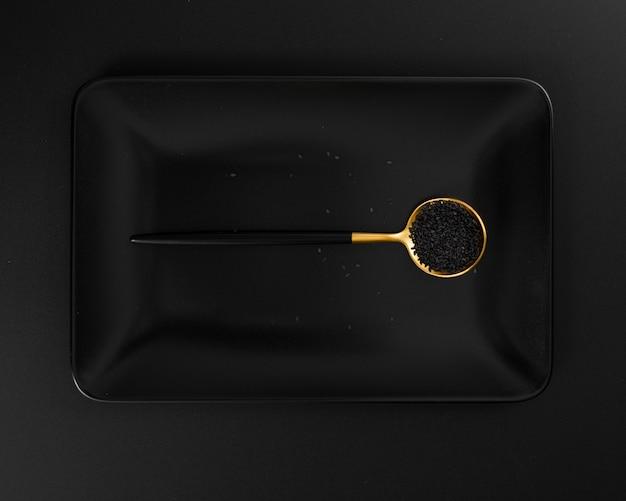 Piatto scuro con un cucchiaio di semi di papavero su uno sfondo scuro
