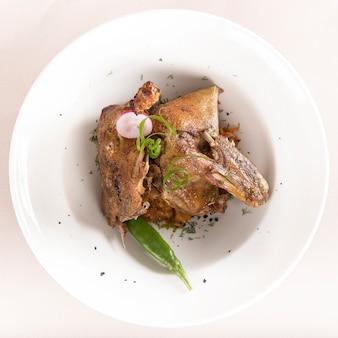 Piatto tradizionale con anatra e cavolo arrostito, decorato con erbe aromatiche
