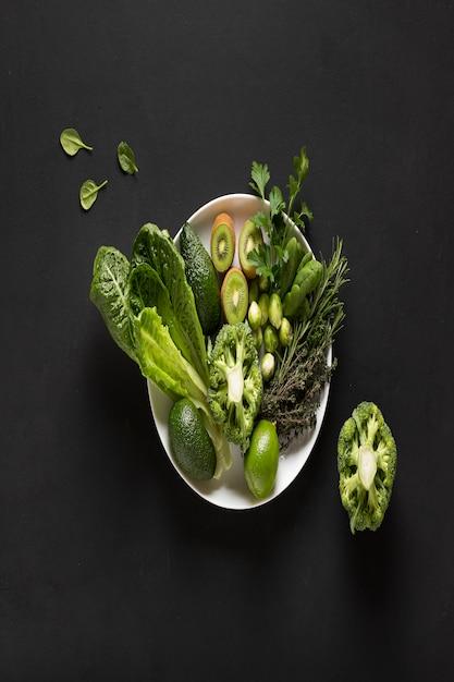 Piatto verde. primo piano verde delle verdure su un piatto bianco. rosmarino, timo, kiwi, broccoli, spinaci, avocado romaine lattuga lime prezzemolo coriandolo