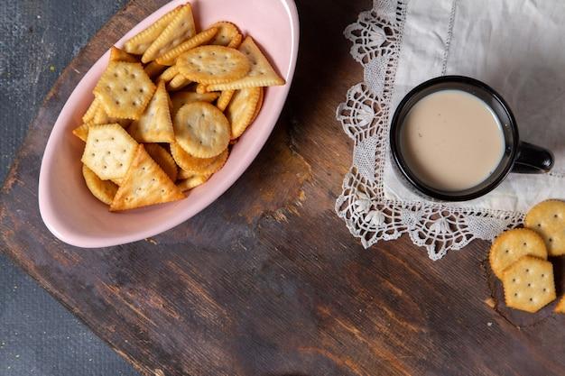 Piatto vista dall'alto con cracker insieme a una tazza di latte sulla foto di cracker snack croccante sfondo grigio